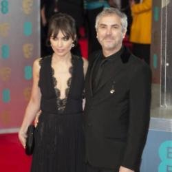 Alfonso Cuarón and his partner Sheherazade Goldsmith arriving at the BAFTAs