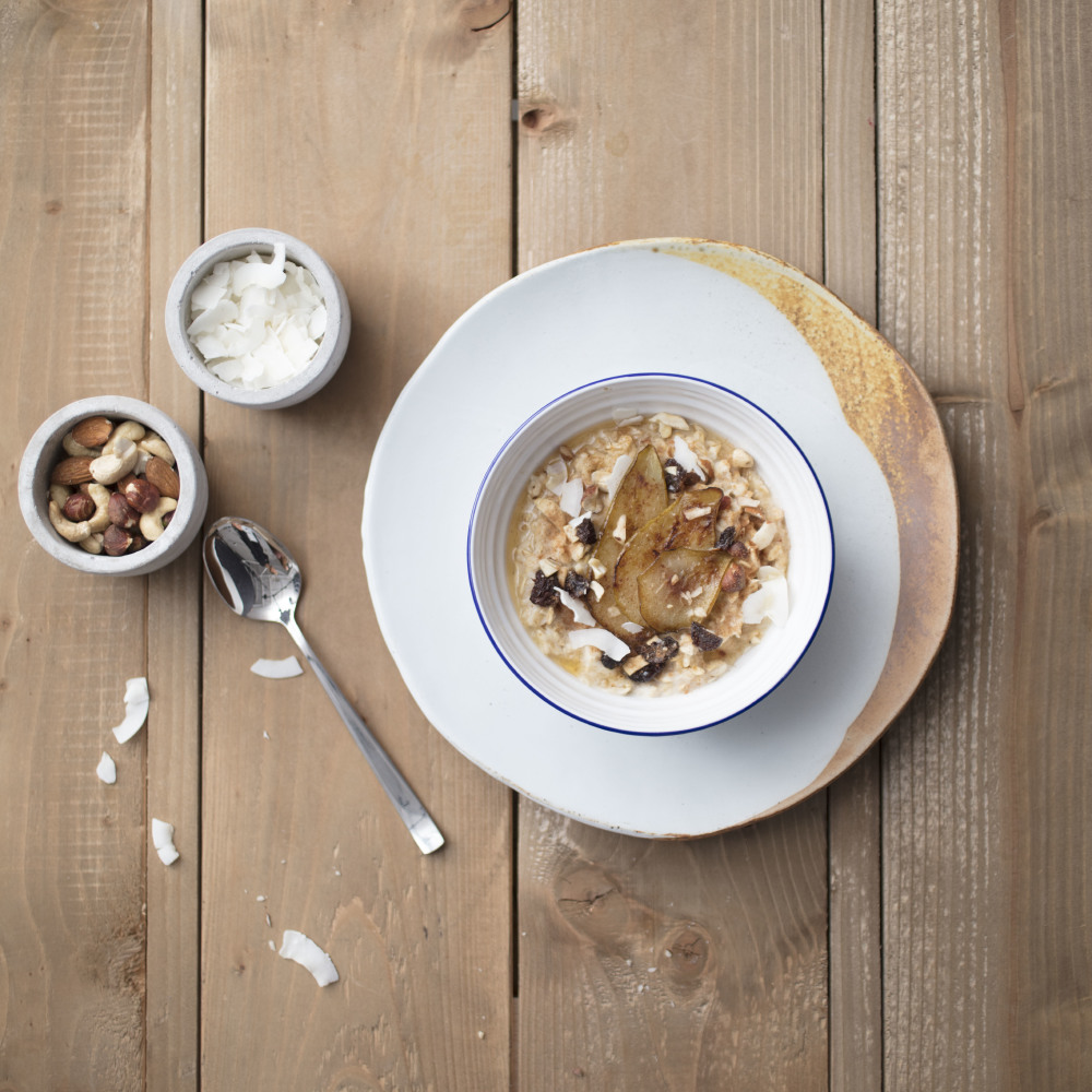 Caramelised pear porridge with cashew nuts and coconut flakes