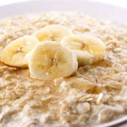 oatmeal porridge topped with slices of banana and a drizzle of honey